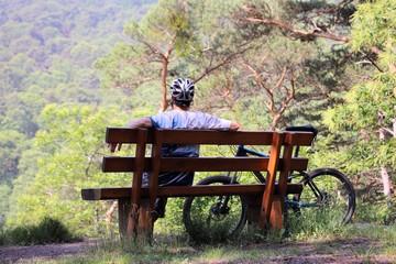 Mountainbiker macht Pause auf einer Bank