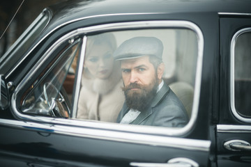 Escort of girl by security. Bearded man and sexy woman in car. Retro collection car and auto repair by mechanic driver. Travel and business trip or hitch hiking. Couple in love on romantic date.