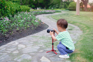 Cute little Asian 2 year old toddler baby boy child  taking photo using a camera & tripod, looking at camera in park, kid photographing nature, Explore & Appreciate Nature with Toddlers concept
