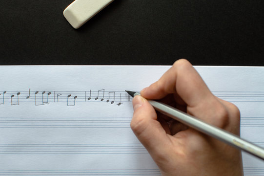Close-up view of the female's hand writing music notes in the music sheets laying on the black background. Concept of the education in arts, music, creativity, music notes writing.