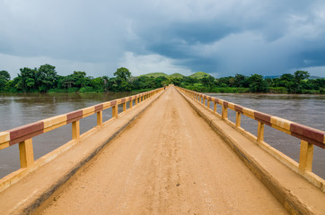 Simple dirt road bridge over tropical river with dramatic clouds in Republic of Congo, Africa