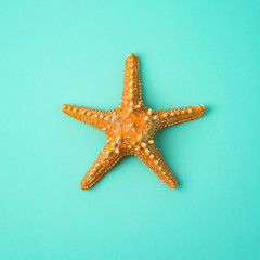 Minimal summer concept. Yellow starfish over blue background. View from above