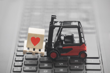 Forklift with red heart symbol on wooden block over laptop keyboard
