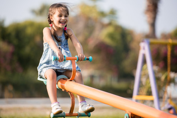 Child Girl Playing At Playground Outdoors In Summer