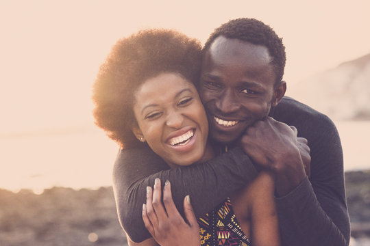 beautiful black race nice model couple man and woman young age hug and stay together with love and friendship. outdoor scenic place near the beach for vacation or lifestyle.