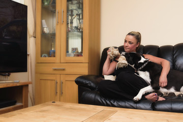 Woman trying to watch TV with her black & white dog on the couch at home in the living room