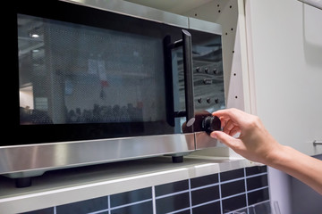 Woman's Hands adjusting timing button on microwave