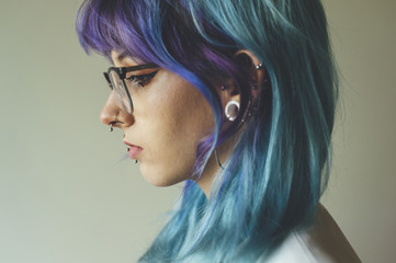 Portrait young woman with blue hair, piercings and glasses
