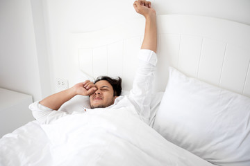 A man waking up in her bed fully rested and open the curtains in the morning to get fresh air.