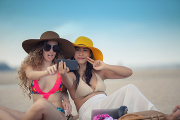 Women are taking photos and Selfie with friends on the sand beach in the summer..