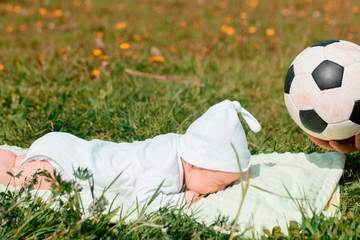 Baby boy infant fun photoshoot soccer football concept big smile having fun playing laughing laying on white furry round through square composition wearing hat white ball beside him mixed race