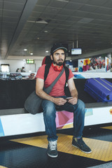 Mid aged man traveller waiting to luggage at bagagge claim in  airport terminal