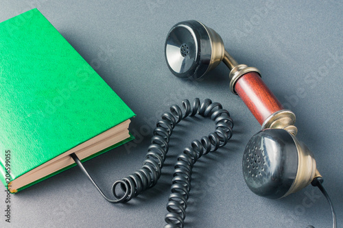 Green book with an old telephone receiver