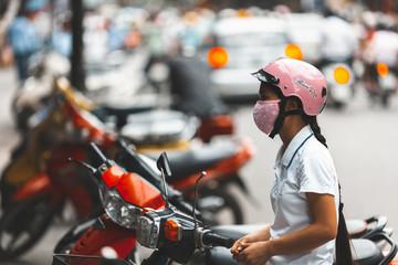 HANOI, VIETNAM. JUNE 28, 2009: Woman waiting on her motorbike in the street of Hanoi, Vietnam