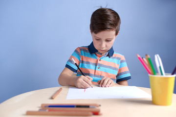 Caucasian boy carefully drawing with colorful pencils.