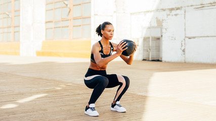Female athlete doing squat exercises with medicine ball