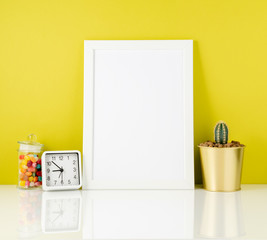 Blank white frame, clock, succulent, candy on white table agains