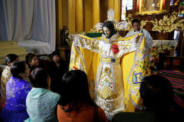 """Devotees of """"Senor del Gran Poder"""" (Lord of Great Power) pray before a parade in his honor in La Paz"""