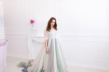 Girl in beautiful dress in white room