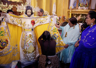 """Devotees fix the cloak of """"Senor del Gran Poder"""" (Lord of Great Power) before a parade in his honor in La Paz"""