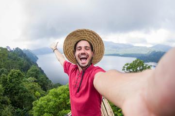 Crazy handsome man taking a selfie on a scenic landscape
