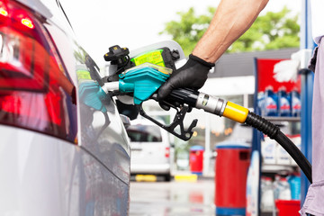 Man filling diesel fuel in car at gas station