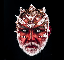 Demon head with evil look. Monster with sharp thorns and warts on face, horror and fantasy concept. Man with white beard and diabolic make-up isolated on black background