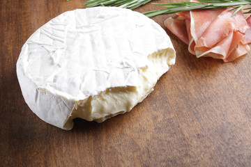 cheese brie and prosciutto jamon ham wooden background rosemary