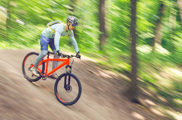 A cyclist in a helmet descends from the mountain on an orange bicycle, motion blur