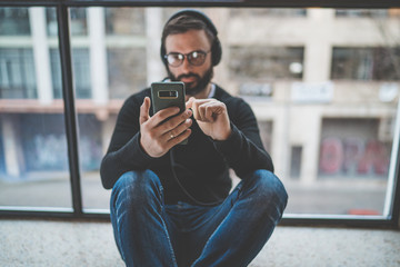 Young bearded man sitting on floor and using mobile phone for listening digital music. Horizontal. Blurred background
