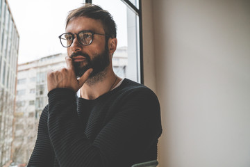 Young handsome man wearing fashion eyeglasses against panoramic windows on blurred background with lots of copy space