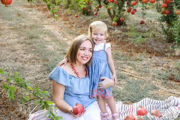 Portrait of happy smiling and laughting mother embracing her cute baby daughter having rest in the pomegrate fruit garden. Harvest, Family vacation concept. Sunset light. selective focus, copy space.