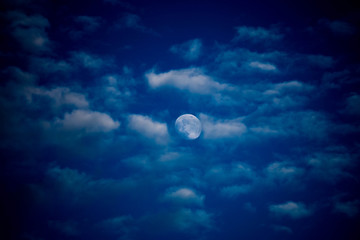 Evening moon behind clouds