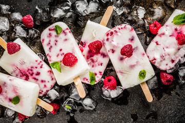 Summer sweet desserts, homemade organic ice cream popsicles from raspberry and yogurt, dark rusty background copy space