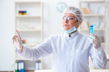 Woman chemist pressing virtual button in lab