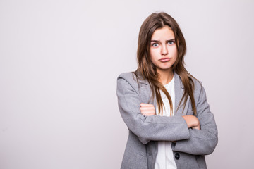 Portrait of an angry serious woman with folded arms isolated on a white background