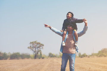 Small boy is sitting on his father's shoulders in the field