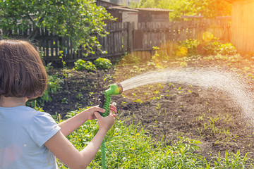 girl watering a garden from a hose