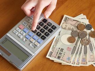計算機でお金の計算をする女性
