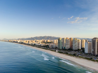 aerial landscape photo of Barra da Tijuca beach , with waves crashing on beach during sunrise, with the beachfront buildings in the background