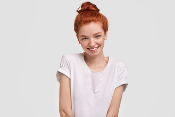 Portrait of happy red haired female being in good mood, wears casual clothing, has shy expression, recieves compliment, stands against white background. Isolated shot. People and skin care concept