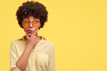 Portrait of good looking hesitant stylish African American female curves lips and holds chin, looks doubtfully aside, poses against light yellow background with blank space. Monochrome concept