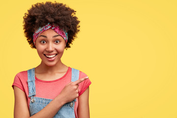 Portrait of delighted African American female, has curly dark hair, dressed in casual clothes, indicates at blank yellow wall as demonstrates announcement, smiles happily at camera. Advertisement