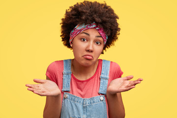 Portrait of hesitant African American female looks clueless, being puzzled, shrugs shoulders, dressed in casual denim overalls, isolated over yellow background. Doubts and puzzlement concept