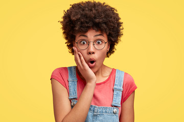 Photo of attractive young female with amazed look, keeps hand on cheek, feels puzzled and surprised as notices something unexpected, has Afro hairstyle, stands indoor against yellow background