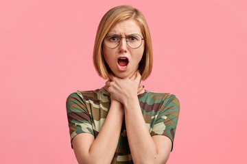 Portrait of shocked beautiful young female suffers from suffocation or makes suicide gesture, keeps both hands on neck, has stressed expression, wears camouflage casual t shirt, stands indoor
