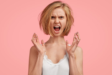 Furious woman being angry as wakes up very early, gestures and shouts loudly with anger, poses against pink studio background. Aggressive irritated young female in low spirit after bad sleep.