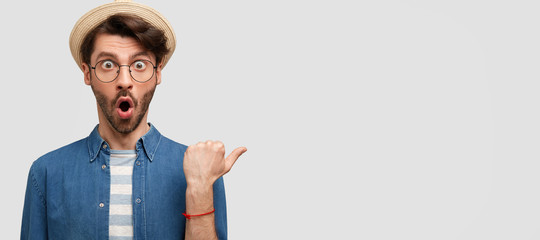 Portrait of amazed attractive young man has shocked expression, wears straw hat and denim shirt, indicates at blank space for your promotional text. Photo of stupefied male farmer wonders indoor