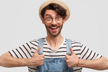 Portrait of happy delighted male gardener keeps thumbs raised, shows his like and approval, wears casual denim overalls and hat, smiles positively, isolated on white background. That`s fine!