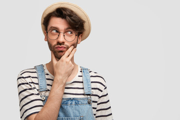 Thoughtful male farmer holds chin and looks pensively asdie, tries to find solution in difficult situation, holds chin, wears casual denim overalls, poses against white blank wall for your promotion